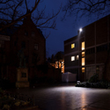 Colour photograph of a building and courtyard lit sparsely by a spotlight