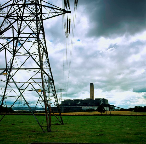 Colour photograph of an electricity pylon with a large energy facility in the background surrounded by fields and a lake