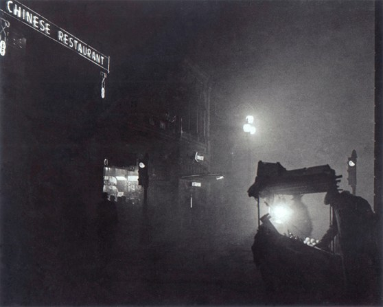 Black and white night time photograph of a street food stall outside a chinese restaurant