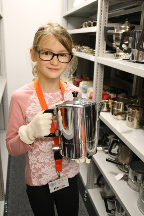 Colour photograph of a young girl holding an early metal kettle