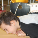 Colour photograph of a young boy demonstrating the use of an old hand held massaging machine