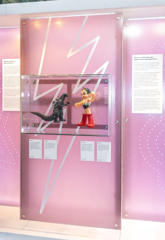 Colour photograph of Godzilla and Astro Boy models on display in a glass case