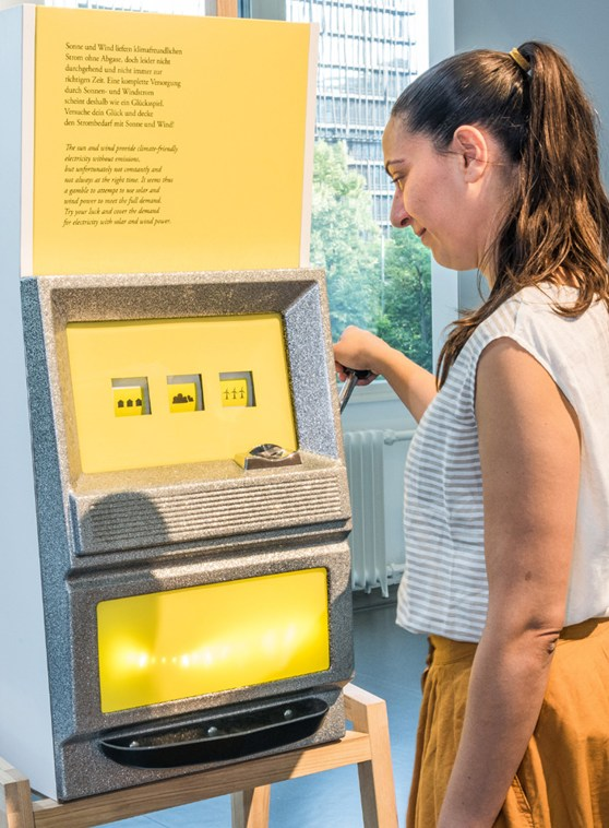 Colour photograph of a museum visitor interacting with a slot machine display case