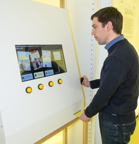 Colour photograph of a museum visitor viewing a digital display