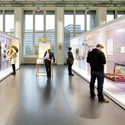 Colour photograph of a bright exhibition space with display objects and visitors