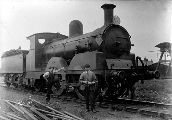 Black and white photograph of two railway engineers standing next to a steam train
