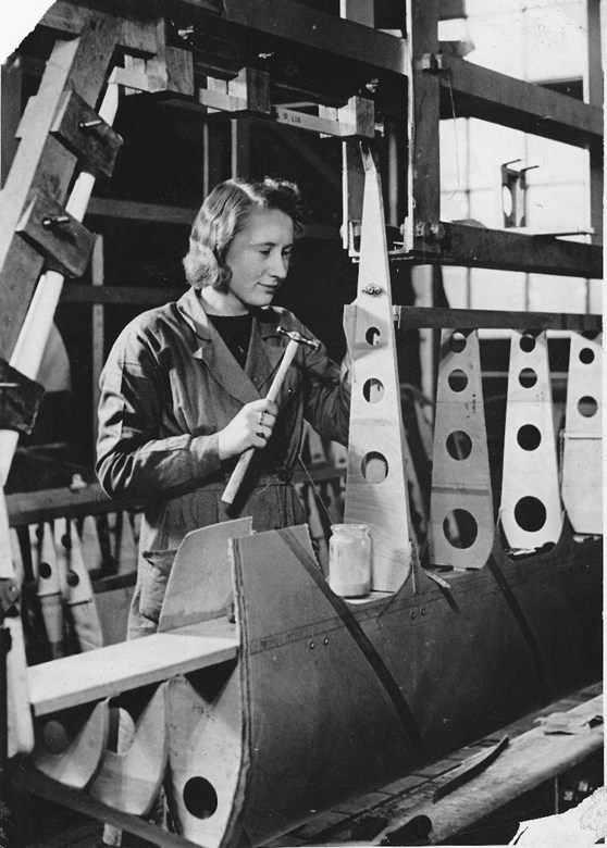 Black and white photograph of a woman working on the construction of an aircraft