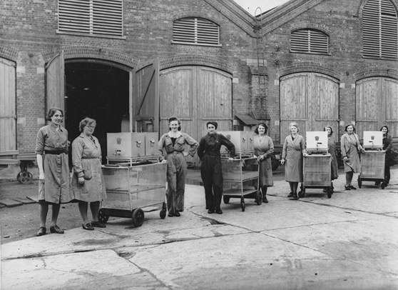 Black and white photograph of a number of women standing with their tea trollies