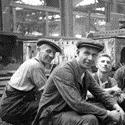 Black and white photograph of a number of male railway workers taking a rest
