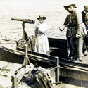 Black and white photograph of Blanche Thornycroft standing in the prow of a pre first world war boat