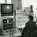 Black and white photograph of a neurologist seated before an EEG with a patient in the adjacent room