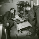 Black and white photograph of William Grey Walter and Ray Cooper at the BNI looking at an EEG