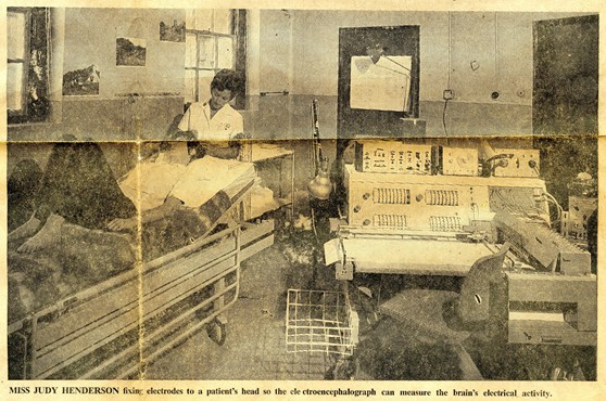 Newspaper clipping showing a nurse fixing electrodes to a patients head in a laboratory