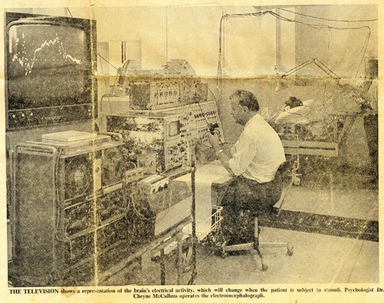 Newspaper clipping showing a psychologist sitting before an electroencephalograph from 1972