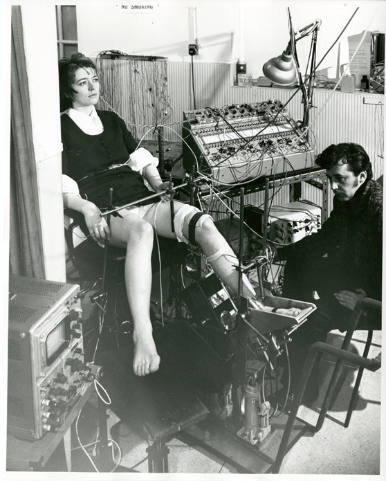 Black and white photograph of a neurologist seated before a female patient