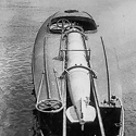 Black and white photograph of a coastal motor boat with a loaded torpedo