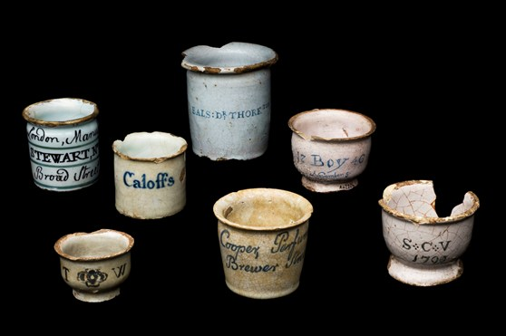 Colour photograph of various nineteenth century tin glazed earthenware dispensing pots