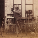 Photographer with two tricycles and two glass plate cameras on tripods from the late nineteenth century