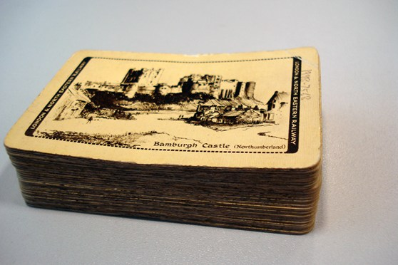 Colour photograph of a pack of playing cards that display a picture of Bamburgh Castle on the underside