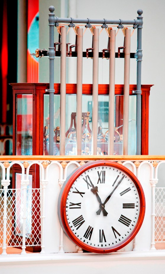 Colour photograph of a working model of a tower clock fitted with five tubular bells