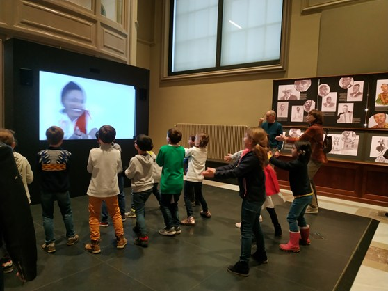Colour photograph of children copying a dance from a screen in a museum gallery