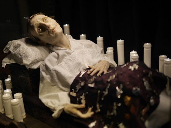 Colour photograph of a sickly wax figure and candles within the Santa Medicina sculpture