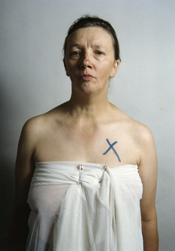Colour photograph of Jo Spence wrapped in a sheet with a black cross over her breast