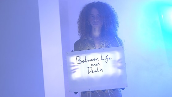 Video still showing a woman holding a sign saying Between Life and Death