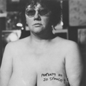 Black and white photograph of a topless Jo Spence with Property of Jo Spence written across her breast