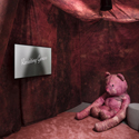 Colour photograph of a video showing in an exhibition room with a large pink teddy bear