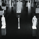 Black and white photograph of stone figure sculptures in a museum